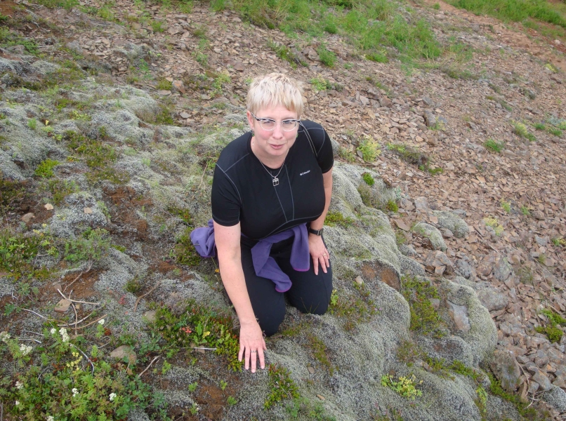 Image of Catherine fondling some wicked-cool blue sub-arctic lichens on a knoll in Iceland near the Geysir hot springs.